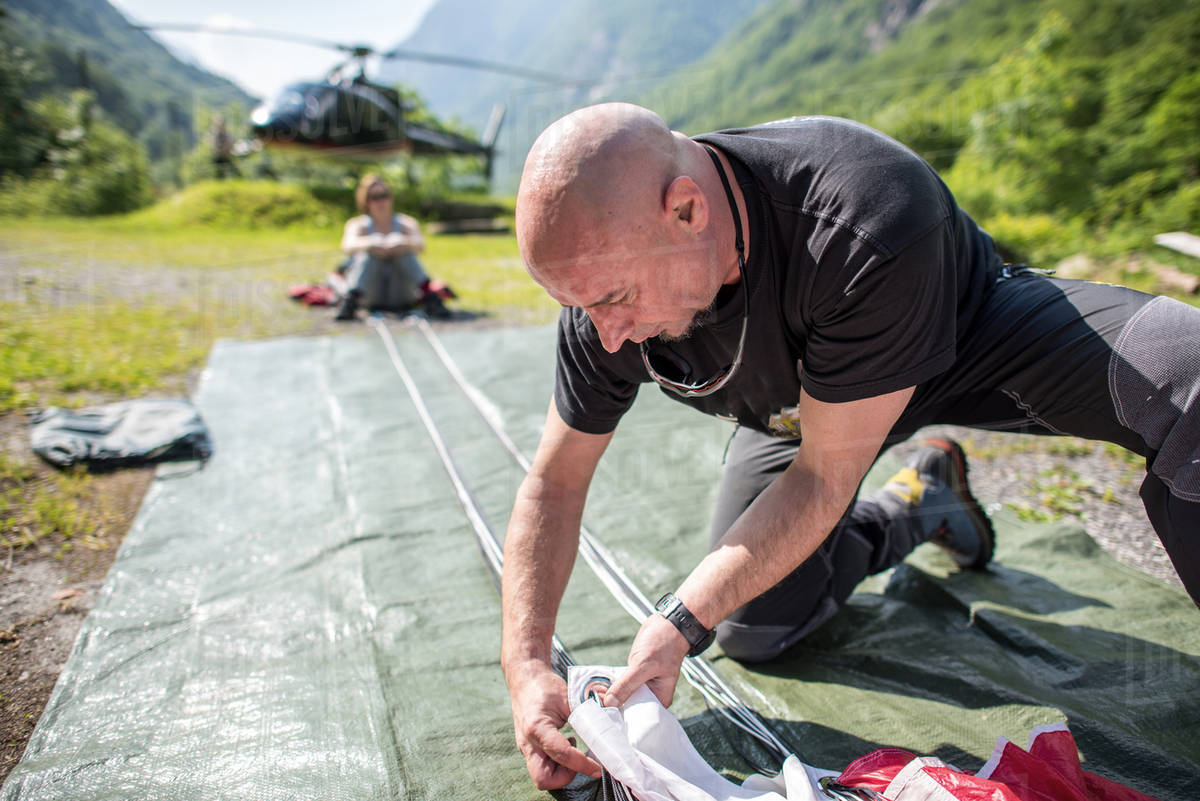 Skydiver arranging his equipment in a field in Ticino canton, Switzerland Royalty-free stock photo