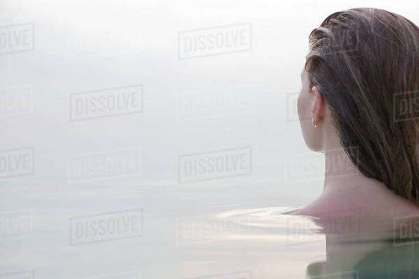 Woman sitting in water viewing the ocean Royalty-free stock photo