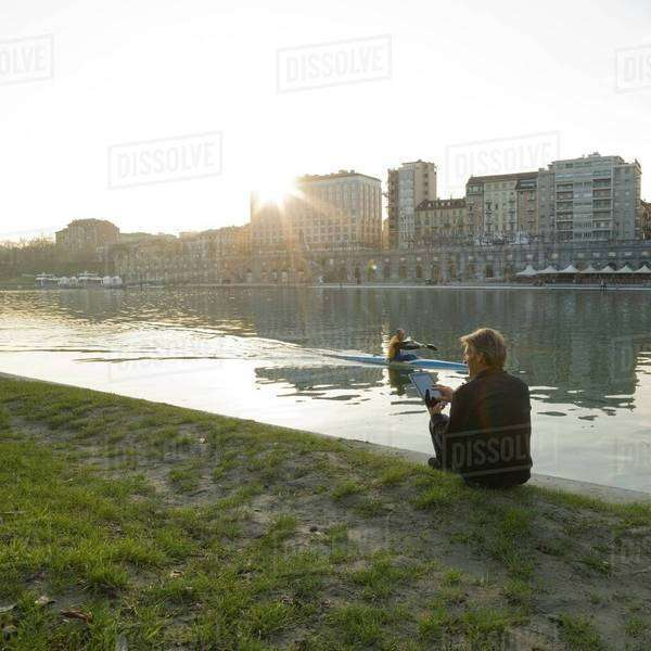 Person using a digital tablet on the riverside in Piedmont, Italy Royalty-free stock photo