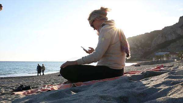 Couple relax on beach, woman sends text Royalty-free stock video