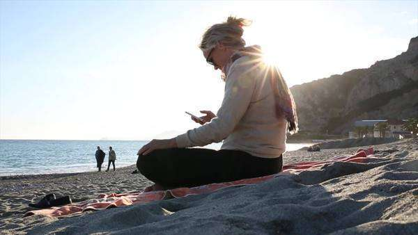 Woman sends text while relaxing on beach Royalty-free stock video