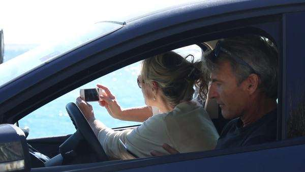 Couple look at digital tablet, take picture of sea from car Royalty-free stock video