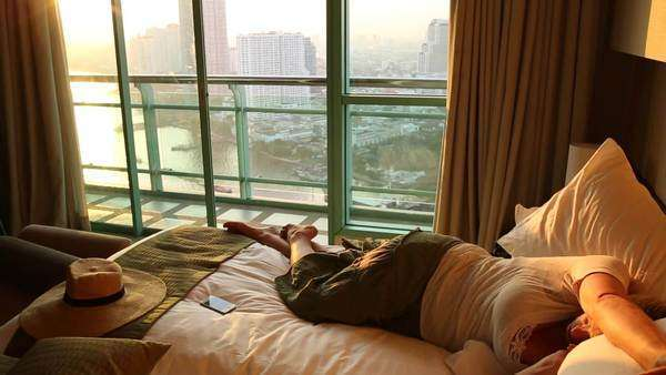 Woman naps on bed in apartment above Chao Phraya, Bangkok Royalty-free stock video