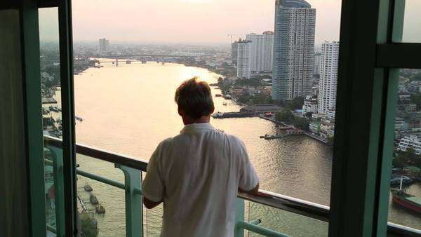 Man with cell phone looks out over Chao Phraya river and Bangkok from balcony Royalty-free stock video