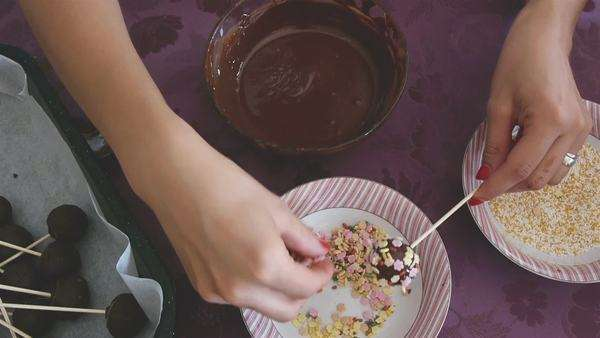Woman Making Tasty Chocolate Cake Pops Dessert With Sprinkles