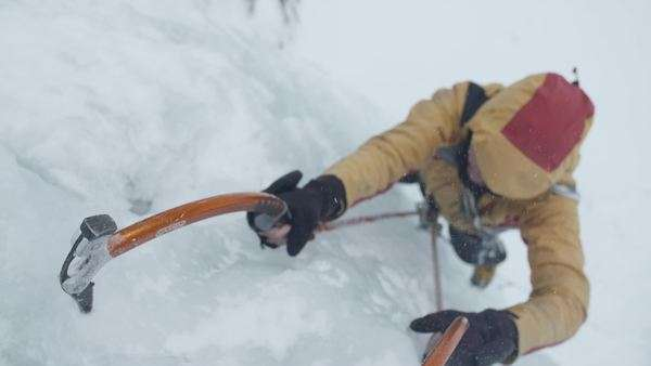 Slow motion of climber putting ice axe into ice Royalty-free stock video