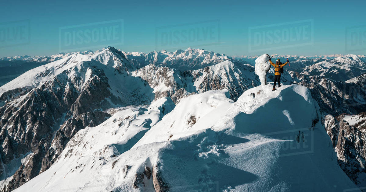 A happy man standing on mountain winter summit with ice axes outstretched, Vrtača, Karavanke, Slovenia Royalty-free stock photo