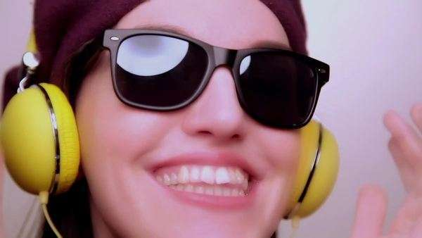 Young Woman Wearing a Purple Beret and Listening to Vintage Yellow DJ Style Headphones tries on Glasses Royalty-free stock video