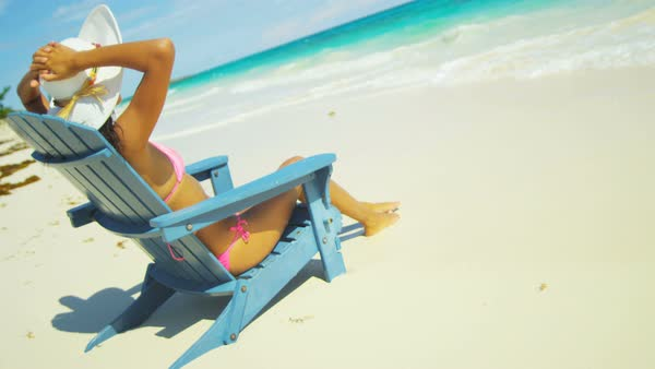 Young ethnic girl sunbathing in a beach chair on a tropical beach Royalty-free stock video