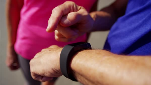 Hands of mature couple using wearable technology on the beach Royalty-free stock video