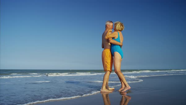 Mature couple in swimsuits dancing on the ocean beach Royalty-free stock video