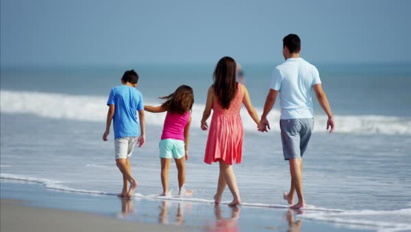 Happy family walking on their beach vacation Royalty-free stock video