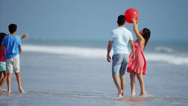 Children enjoying vacation with parents playing with red ball on beach Royalty-free stock video