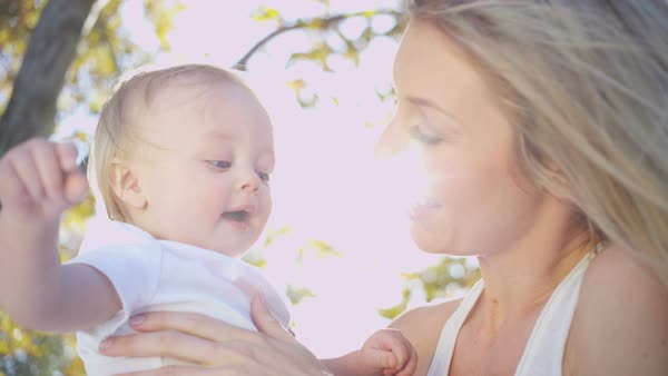Attractive blonde young Caucasian mum holding her blue eyed baby boy while he plays with her hair outdoors Royalty-free stock video