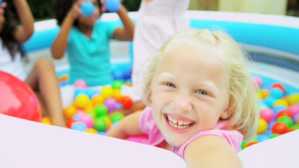 Portrait of happy cute Caucasian American girl having fun with her friends in colored ball pool  Royalty-free stock video