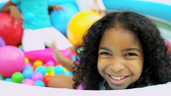 Portrait of smiling African American girl playing with her friends in ball pool together Royalty-free stock video