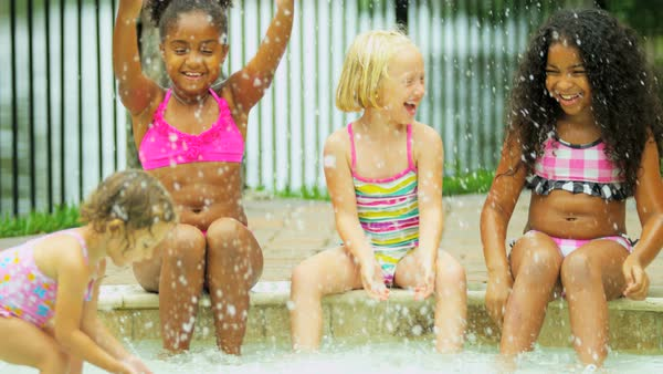 Laughing little cute multi ethnic girls wearing swimsuits playing in swimming pool outdoors Royalty-free stock video