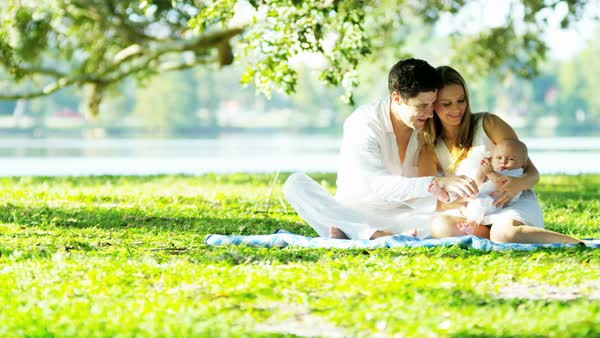 Young attractive European parents and their young baby son enjoying picnic outdoors in the park Royalty-free stock video