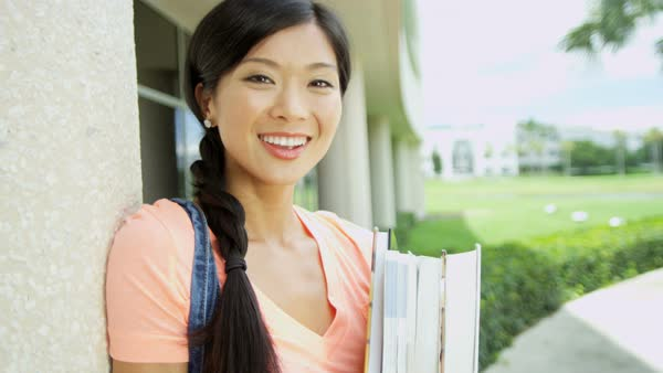 Portrait of happy young Asian American female student holding workbook standing before modern block college campus  Royalty-free stock video
