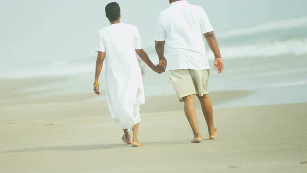 Happy mature African American couple enjoying their peaceful retirement lifestyle walking on the beach holding hands  Royalty-free stock video