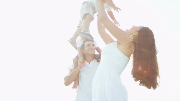 Carefree young Hispanic parents enjoying togetherness strolling on the beach with their young sons Royalty-free stock video