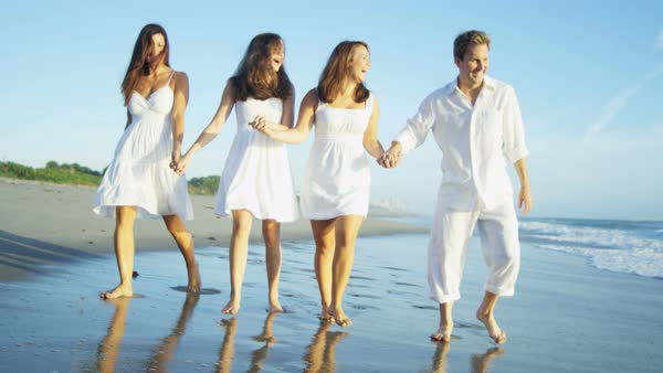 A carefree Caucasian American family happy with their beach destination walking in the wet shallows Royalty-free stock video