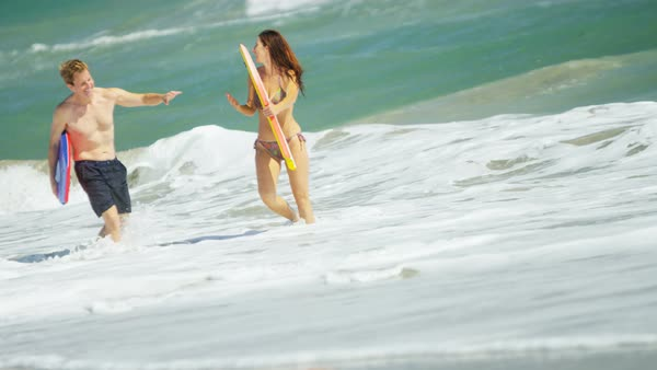 Carefree Caucasian American couple having fun in the waves of the ocean on vacation Royalty-free stock video