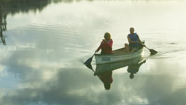 Healthy senior Caucasian American couple outdoors in the kayak on the lake paddling and enjoying the sunset  Royalty-free stock video