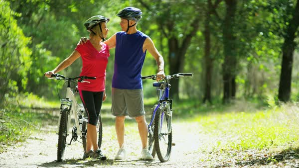 Active Caucasian American seniors enjoying bike ride to keep healthy outdoors in the forest Royalty-free stock video