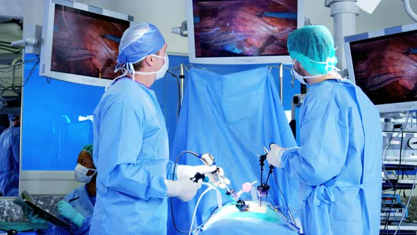 Professional African American hospital specialist team in scrubs in the operating theatre performing Laparoscopy surgery using video monitor playback and Endoscope and Laparoscope instruments Royalty-free stock video