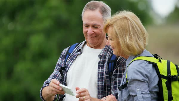Happy senior Caucasian European couple wearing casual clothing enjoying hiking watching photo on smartphone Royalty-free stock video