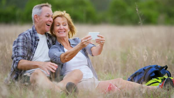 Happy senior Caucasian American couple having fun taking selfie on smart phone in the countryside outdoors Royalty-free stock video