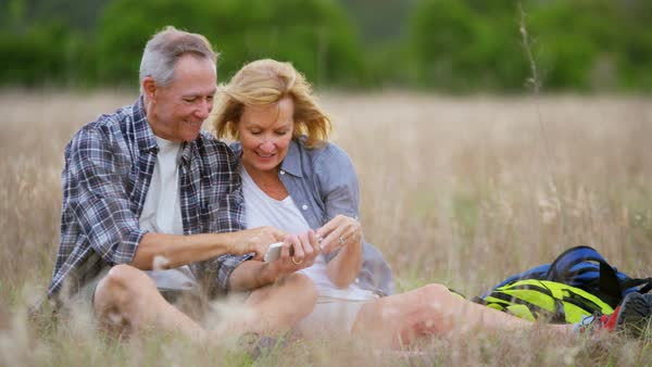 Mature Caucasian American couple taking picture on smartphone enjoying their outdoor lifestyle sitting in the countryside outdoors Royalty-free stock video