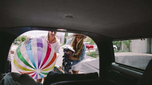Friends open the trunk and wave hello to the camera as they put away a beach ball. Royalty-free stock video