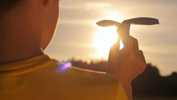 Boy throws a paper plane, freedom, sunset, close-up Royalty-free stock video