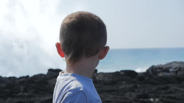 Slow motion of a boy watching crashing waves Royalty-free stock video