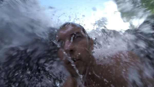 Man standing under a gushing Hawaiian waterfall. Royalty-free stock video