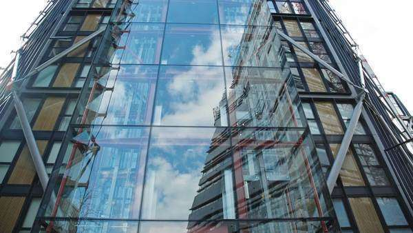 Modern building with a glass facade in urban environment. The surrounding buildings and clouds from the sky reflect in the windows. Construction site next to the Tate Modern reflecting on glass facade Royalty-free stock video