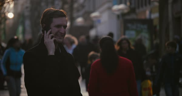 Back lit man talking on cell phone on busy city street in cold weather  Royalty-free stock video