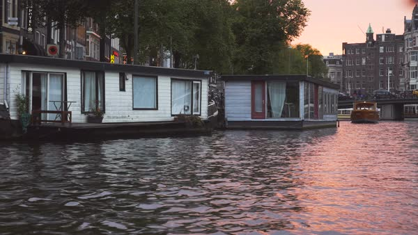 Amsterdam houseboats and apartment buildings filmed while sailing on a canal. The setting sun gives a pinkish glow to the waters.  Royalty-free stock video