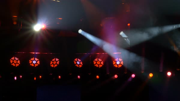 A row of LED stage lights shine directly at the camera. Beam lights move above and below.  Royalty-free stock video