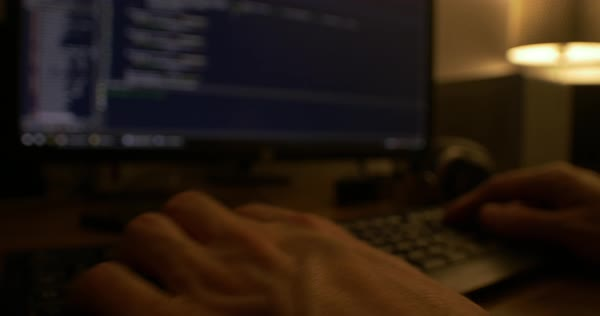 Dark static shot of a programmer typing on a keyboard and the screen visible in the background. Royalty-free stock video