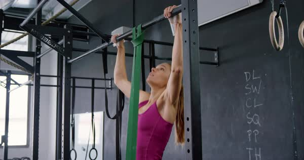 Medium shot of a young fit woman doing pull-ups in the gym Royalty-free stock video