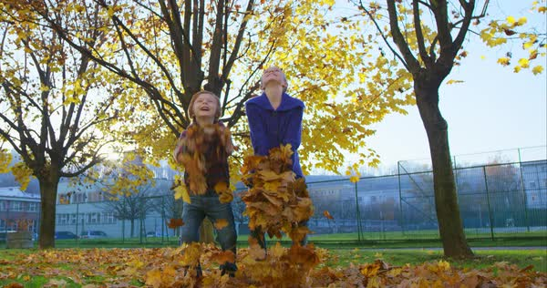 Happy brother and sister throwing yellow autumn leaves in the air Royalty-free stock video