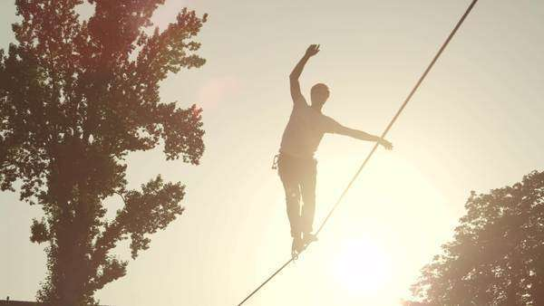 Young unrecognizable man walking on high slackline at beautiful summer sunset Royalty-free stock video