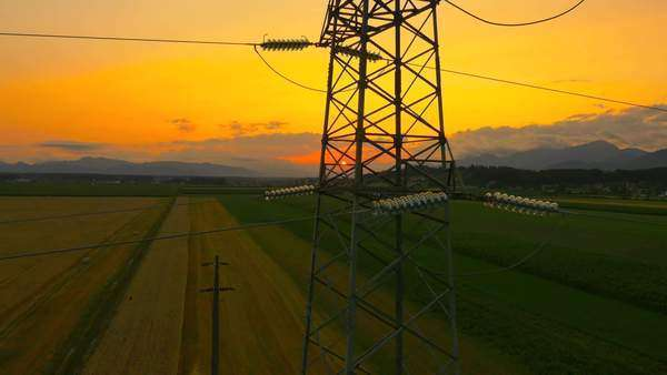 Aerial - Flying up the high voltage electricity tower and power lines at sunset above the beautiful agricultural field Royalty-free stock video