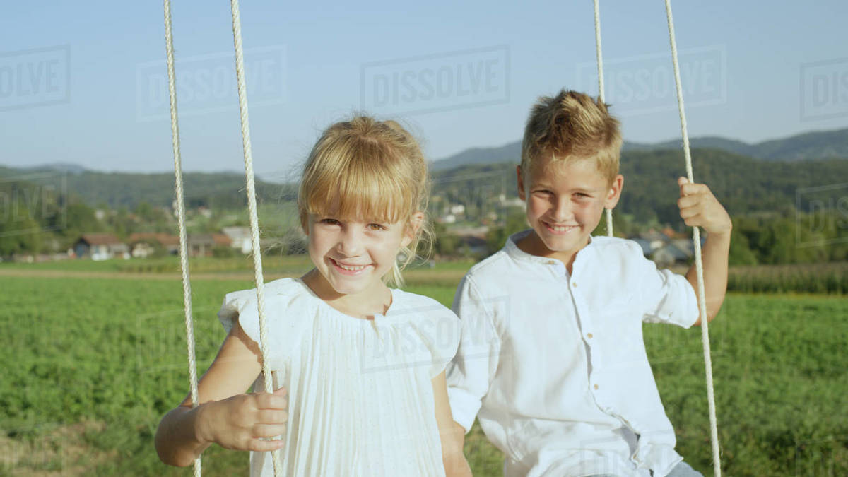 Playful brother and sister having fun swinging barefoot under a big tree on warm sunny day in summer. Smiling young boy and girl enjoying their free time swaying on a wooden swing in the sun Royalty-free stock photo