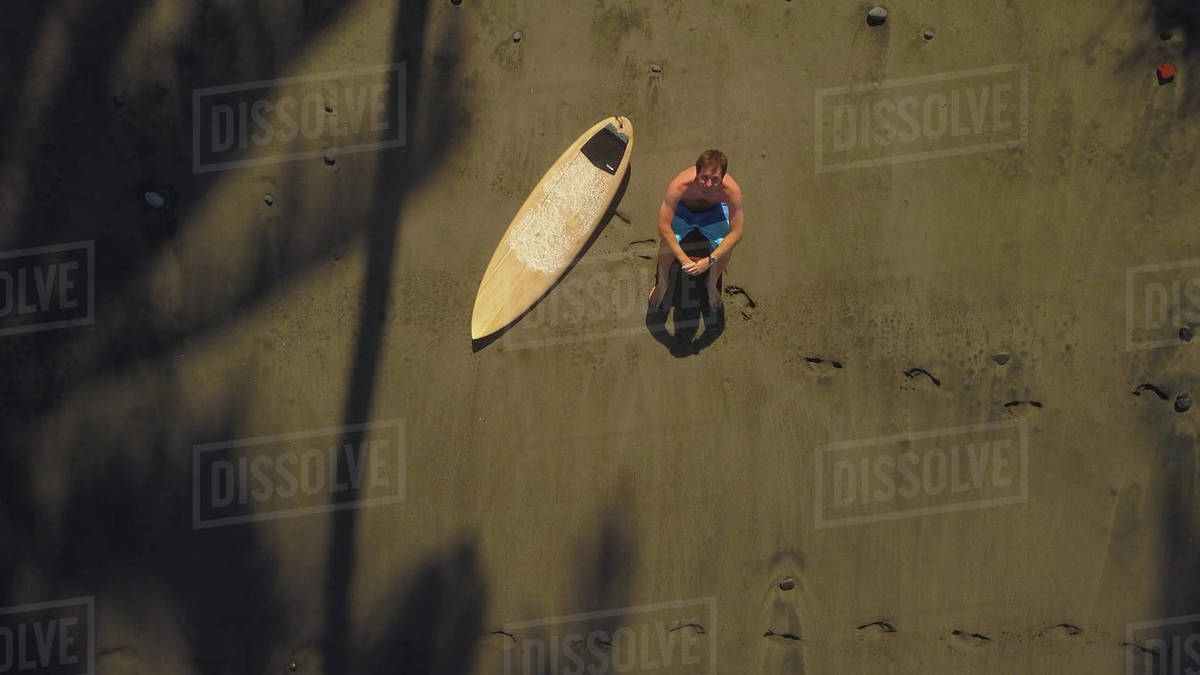 Lonely topless surfer sitting on sandy beach, looking into the horizon. Unrecognizable man sitting next to wooden surfboard on remote sandy beach on cool tropical island in Indonesia Royalty-free stock photo