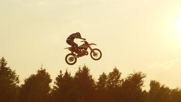 Extreme pro motocross rider riding fmx motorbike, jumping huge jump performing dangerous stunt against the sky. Professional motocross biker jumps big air trick over golden sunset sun Royalty-free stock video