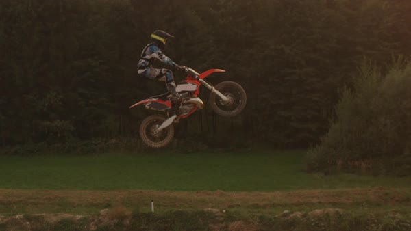 Extreme pro motocross rider riding fmx motorbike, jumping big air kicker, performing dangerous stunt. Professional motocross biker jumps no hander trick over golden evening sun. Royalty-free stock video
